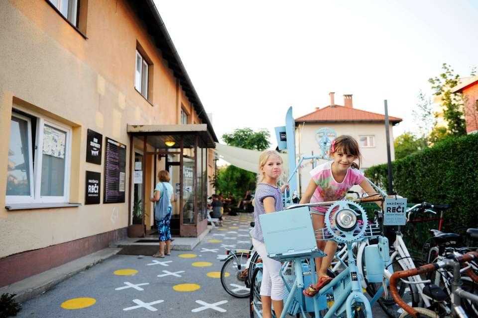 Kinder spielen vor dem Treffpunkt Leihladen in Ljubljana auf einer Fahrrad-Skulptur aus alten Bautteilen